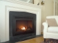 The gel firebox is surrounded by a custom wood and stone mantel.